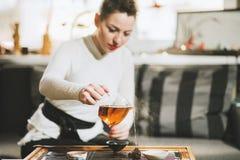 Beautiful girl brews tea for visitors in coffee. Beautiful girl brews tea for customers in a cafe Stock Image