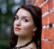 Beautiful girl by the brick wall Stock Image