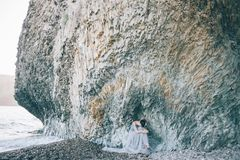Free Beautiful Girl Bride In A Long Blue Dress Sitting On The Sea Near The Cliff With His Head Bowed, Stock Photos - 116621853