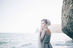 Beautiful girl bride in a long grey dress with lace,with a veil on the beach, near the rock, closed with a veil, viewing profile,. Horizontal Stock Images