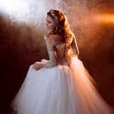 Beautiful girl bride in luxurious wedding dress, portrait in Golden tones, effects of glare. Beautiful girl bride in a luxurious wedding dress, portrait in Royalty Free Stock Image