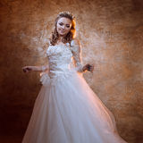 Beautiful girl bride in luxurious wedding dress, portrait in Golden tones. Beautiful girl bride in a luxurious wedding dress, portrait in Golden tones, the Royalty Free Stock Photography