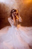 Beautiful girl bride in luxurious wedding dress sitting on the floor, portrait in Golden tones, effects of glare. Beautiful girl bride in a luxurious wedding Stock Images