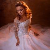 Beautiful girl bride in luxurious wedding dress sitting on the floor, portrait in Golden tones, effects of glare. Beautiful girl bride in a luxurious wedding Royalty Free Stock Photos