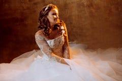 Beautiful girl bride in luxurious wedding dress sitting on the floor, portrait in Golden tones, effects of glare. Beautiful girl bride in a luxurious wedding Royalty Free Stock Photo