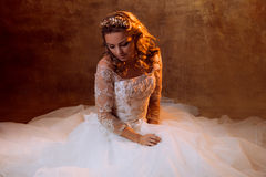Beautiful girl bride in luxurious wedding dress sitting on the floor, portrait in Golden tones, effects of glare. Beautiful girl bride in a luxurious wedding Royalty Free Stock Images