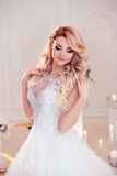 Beautiful girl bride in a magnificent dress. Luxurious light interior Royalty Free Stock Image