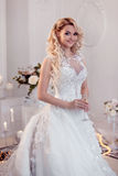 Beautiful girl bride in a magnificent dress. Luxurious light interior Stock Photos