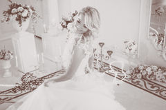 Beautiful girl bride in a magnificent dress. Luxurious light interior. Ochre toning Stock Photo