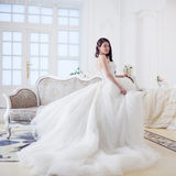 Beautiful girl bride in a magnificent dress sitting on the sofa. Luxurious light interior Royalty Free Stock Image
