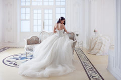 Beautiful girl bride in a magnificent dress sitting on the sofa. Luxurious light interior Stock Photo