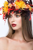 Beautiful girl with bright autumn wreath of. Leaves and flowers. Beauty face. Picture taken in the studio on a white background royalty free stock photography
