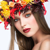 Beautiful girl with bright autumn wreath of. Leaves and flowers. Beauty face. Picture taken in the studio on a white background royalty free stock images
