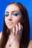 Beautiful girl with bright blue makeup and jewelery Stock Photos