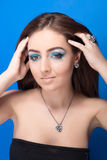 Beautiful girl with bright blue makeup and jewelery Stock Image