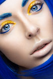 Beautiful girl in a bright blue wig in the style of cosplay and creative makeup. Beauty face. Art image. Picture taken in the studio on a yellow background Royalty Free Stock Images