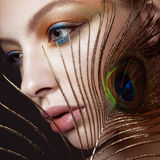 Beautiful girl with bright colored makeup and peacock feather on her face. Beauty. Close-up Royalty Free Stock Image