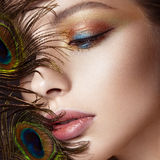 Beautiful girl with bright colored makeup and peacock feather on her face. Beauty. Close-up Royalty Free Stock Photos