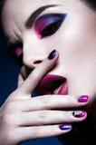 Beautiful girl with bright creative fashion makeup and colorful nail polish. Art beauty design. Stock Photos