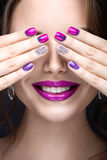 Beautiful girl with a bright evening make-up and purple manicure with rhinestones. Nail design. Beauty face. Picture taken in the studio on a black background royalty free stock image
