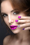 Beautiful girl with a bright evening make-up and purple manicure with rhinestones. Nail design. Beauty face. Royalty Free Stock Image