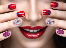 Beautiful girl with a bright evening make-up and red manicure with rhinestones. Nail design. Beauty face. Stock Photo