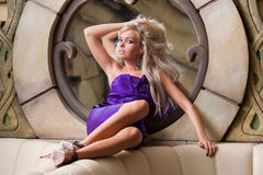 A beautiful girl with bright golden hair styled in vintage look, dressed in pink cocktail dress, expensive shoes near the mirror Stock Image