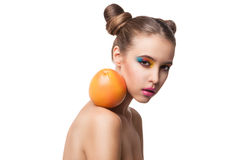 Beautiful girl with bright make-up and grapefruit on bare shoulder. Portrait of young girl with grapefruit on bare shoulder.Isolated Stock Photography