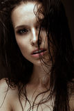 Beautiful girl with a bright make-up, wet hair and skin. Beauty face. Royalty Free Stock Photography