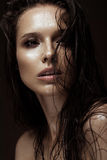 Beautiful girl with a bright make-up, wet hair and skin. Beauty face. Royalty Free Stock Photos