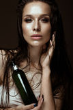 Beautiful girl with a bright make-up, wet hair and skin, bottle of cosmetic products in hands. Beauty face. Stock Photography