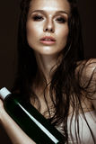 Beautiful girl with a bright make-up, wet hair and skin, bottle of cosmetic products in hands. Beauty face. Stock Image