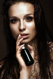 Beautiful girl with a bright make-up, wet hair and skin, bottle of cosmetic products in hands. Beauty face. Stock Images