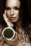 Beautiful girl with a bright make-up, wet hair and skin, bottle of cosmetic products in hands. Beauty face. Stock Photos