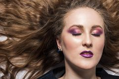 Beautiful girl with bright makeup, closed eyes and long curly blond hair, horizontal, concept is cosmetics and hair, close-up stock image