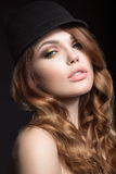 Beautiful girl with bright makeup and curls in a hat. Beauty face. Royalty Free Stock Photo