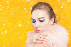 Beautiful girl with bright makeup dressed in luxury fur coat. Fashion girl with bright makeup like a Russian flag, dressed in luxury fur coat on a yellow Stock Image