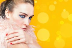 Beautiful girl with bright makeup dressed in luxury fur coat. On a yellow background. Winter. Fashion. Color nails. Copy space. Blur Royalty Free Stock Photo