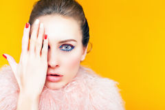 Beautiful girl with bright makeup dressed in luxury fur coat. On a yellow background. Winter. Fashion. Color nails. Copy space. Looking at camera Royalty Free Stock Photos
