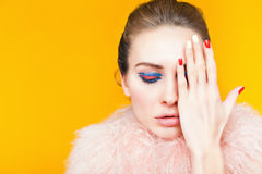 Beautiful girl with bright makeup dressed in luxury fur coat. On a yellow background. Winter. Fashion. Color nails. Copy space. Looking at camera Stock Images