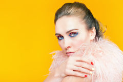 Beautiful girl with bright makeup dressed in luxury fur coat. On a yellow background. Winter. Fashion. Color nails. Copy space. Looking at camera Royalty Free Stock Image
