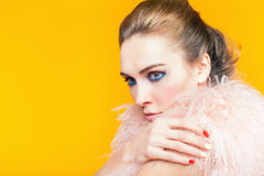 Beautiful girl with bright makeup dressed in luxury fur coat. On a yellow background. Winter. Fashion. Color nails. Copy space. Looking at camera Stock Image