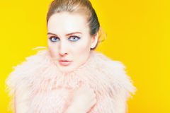Beautiful girl with bright makeup dressed in luxury fur coat. On a yellow background. Winter. Fashion. Copy space. Looking at camera Stock Photos