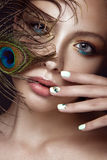 Beautiful girl with bright makeup, manicure design and peacock feather on her face. Art nails. Royalty Free Stock Photo