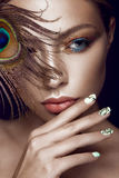 Beautiful girl with bright makeup, manicure design and peacock feather on her face. Art nails. Stock Photo