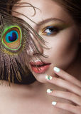 Beautiful girl with bright makeup, manicure design and peacock feather on her face. Art nails. Stock Photos