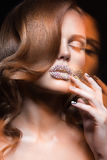 Beautiful girl with bright nails and lips of crystals, long eyelashes and curls. Beauty face. Royalty Free Stock Photo