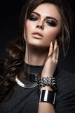 Beautiful girl with bright smokey make-up, perfect. Skin, black clothes, metal accessories and hairstyle as a braid. Picture taken in the studio on a gray Stock Image
