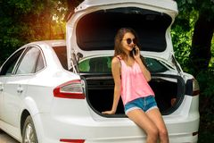 Beautiful girl in a bright t-shirt and shorts sitting in the trunk of a car Royalty Free Stock Images