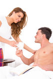 Beautiful girl bringing coffee to her man in bed royalty free stock images